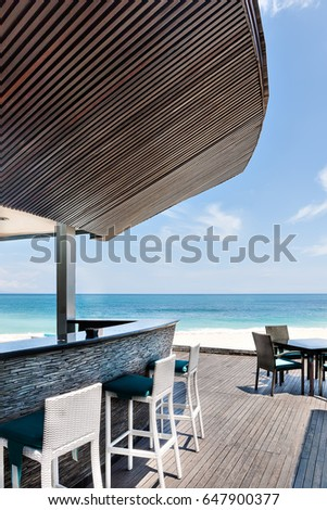 Ocean side restaurant with chairs and table giving the view of the view of the horizon including blue water and sky #647900377