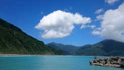 Ocean side view - ocean, small harbor and mountain under blue sky with cloud (Fenniaolin Fish Harbor/Pigeon-Forest Fishing Harbor)