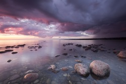 Ocean sunrise scene from the southern of Sweden, large rocks in forground