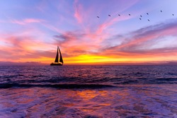 Ocean sunset sailboat silhouette is sailboat sailing along the ocean water with a colorful vivid sunset sky and silhouettes of birds flying in the background..