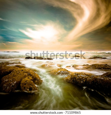 Ocean surge with rocks under a dramatic sky.