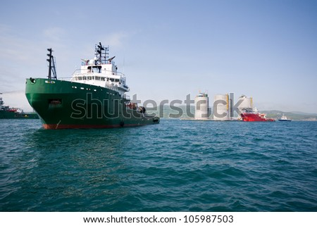 Ocean tugs towing base offshore oil drilling platform. Sea of Japan. Russian coast.