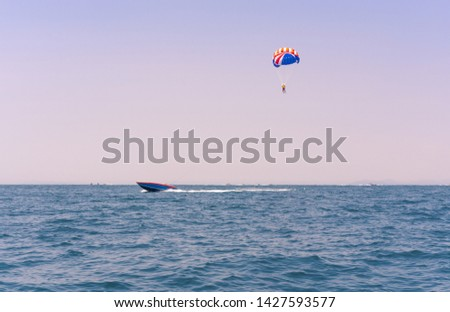 Ocean view of a man Parasailing in the sea towed by a speedboat in american colors - Watersports summer activity of a boat towing a parasail above water at twilight with USA stars & stripes - image #1427593577