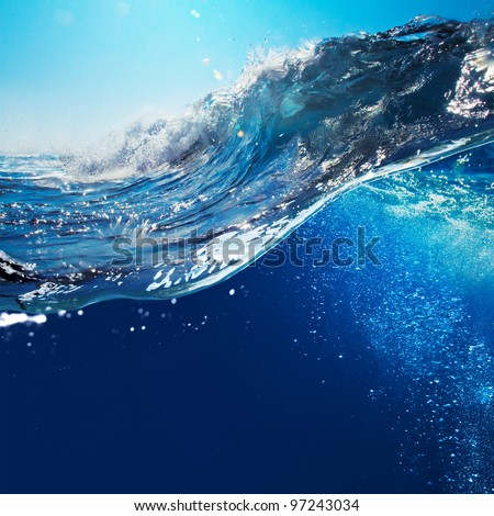 ocean-view seascape landscape with blue sky and sunlight big curly ocean wave splitted by waterline to underwater part with air bubbles #97243034