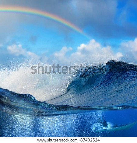 Ocean view splitted underwater side with mantaray surrounded by air bubbles and shore break big waves with colored rainbow