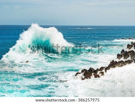 Ocean wave background breaking sea water rocky shore rough seas turquoise water gradient foam, Porto Moniz Madeira #386257975