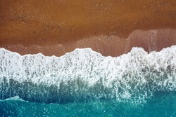 ocean wave on a sandy beach, background  top view of sea