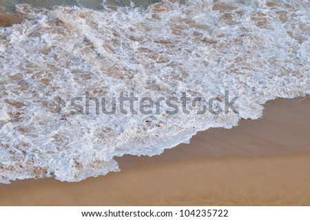 Ocean wave onto shore with beautiful foam patterns. Australia