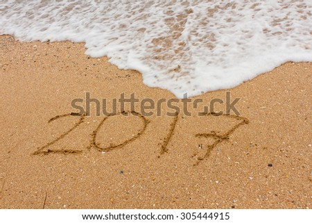 Ocean wave washes inscription 2017 on seashore. #305444915