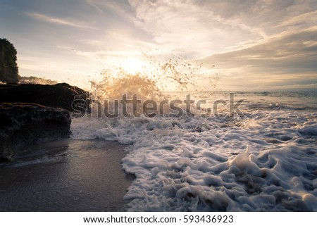 Ocean wave with foam beating against the rocks at sunset. The beautiful landscape of the elemental power of water. Bali Indonesia #593436923