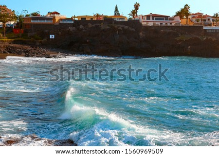 Ocean waves on the coast of the island at sunset. Seaside resort.