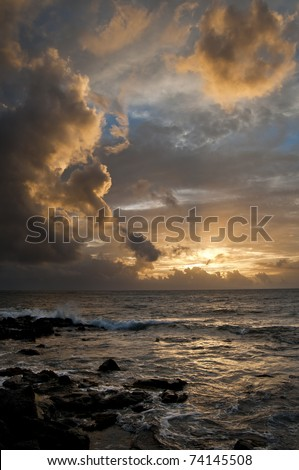 Ocean with a golden sunset shining through the Hawaii clouds