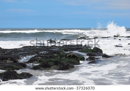 Ocean with rock jetty and splashing wave