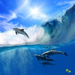 Oceanview with sunlight. A flock of playful dolphins swimming underwater and one of them leaping out from big sea surfing wave