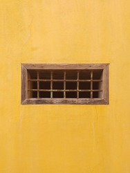 Ocher wall with old small rectangular window with iron bars. Old window on yellow cement wall. Architecture and construction detail. Masonry pattern.