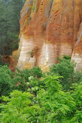 Ochre cliffs and lush foliage below the town of Roussillon, Roussillon, Vaucluse, Provence-Alpes-Côte d'Azur, France