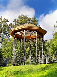 Octagonal gazebo on a metal base behind a forged metal fence against the backdrop of trees