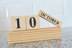 October 10, Cover design with number cube on a white background and granite table.