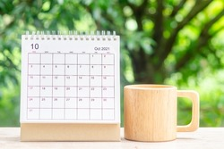 October month, Calendar desk 2021 for organizer to planning and reminder on wooden table with green nature background.