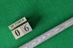 October 6, Number cube With a snooker stick on a green background, snooker table.