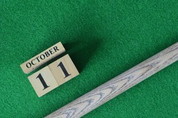 October 11, Number cube With a snooker stick on a green background, snooker table.