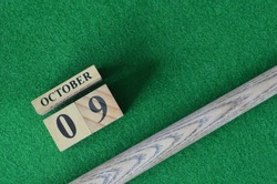 October 9, Number cube With a snooker stick on a green background, snooker table.