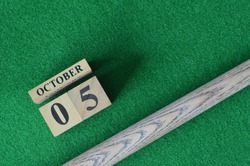 October 5, Number cube With a snooker stick on a green background, snooker table.