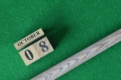 October 8, Number cube With a snooker stick on a green background, snooker table.