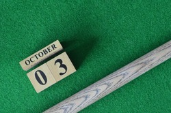 October 3, Number cube With a snooker stick on a green background, snooker table.