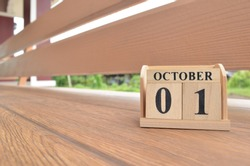 October 1, Number cube with wooden balcony background.