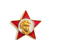 October school lapel badge of the times of the USSR, covered with red enamel and with a portrait of Lenin in childhood, isolated on a white background