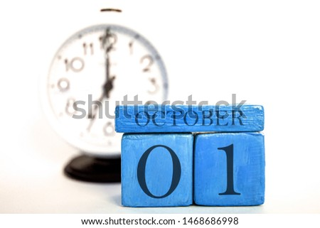 october 1st. Day 1 of month, handmade wood cube calendar and alarm clock on blue color. autumn month, day of the year concept. #1468686998