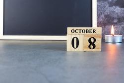 October 8th. Hello October, Cube wooden calendar showing date on 8 October, Wooden calendar with date on a dark background.