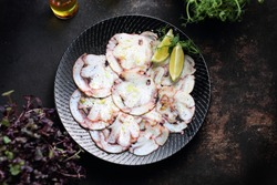 Octopus carpaccio. Seafood dish. A plate with an appetizing dish. Application suggestion. Culinary photography, food stylization.
