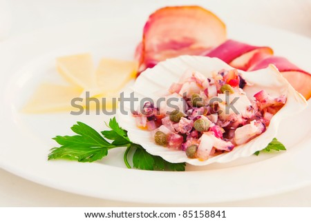 Octopus salad served with cheese and prosciutto on the side (shallow dof) - stock photo