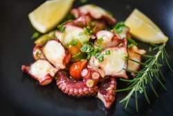 Octopus salad with lemon tomatoes rosemary and vegetables on plate, Fresh and healthy salad seafood squid and octopus