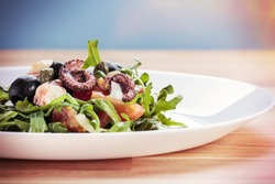 Octopus salad with rucola, olives and feta cheese on white plate. Post processed with vintage filter.