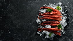 Octopus tentacles lie on ice on a black stone background. Seafood. Top view. Flat lay.