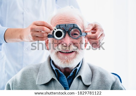 Oculist putting ophthalmic glasses on smiling elderly male patient Zdjęcia stock ©