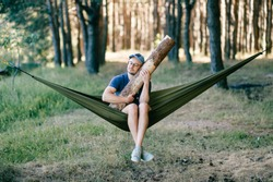 Odd weird strange unusual male person. Outlandish funny crazy foolish man sleeping in hammock with huge wooden log at nature among trees.  Wood and forest lover. With beam in bed.  Leisure lifestyle