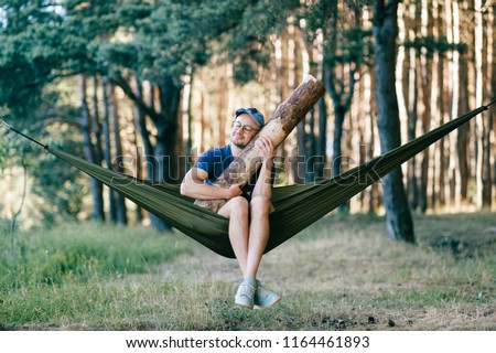 Odd weird strange unusual male person. Outlandish funny crazy foolish man sleeping in hammock with huge wooden log at nature among trees.  Wood and forest lover. With beam in bed.  Leisure lifestyle Сток-фото ©