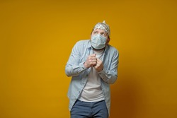 Oddball man in a medical mask is very afraid of contracting the virus, he put on a tin foil hat and looks upstairs in dismay.