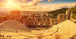 Odeon of Herodes Atticus at sunset, Athens, Greece. It is old famous landmark of Athens. Scenic panorama of ancient Greek monument overlooking Athens city. Sunny panoramic view of classical theater.