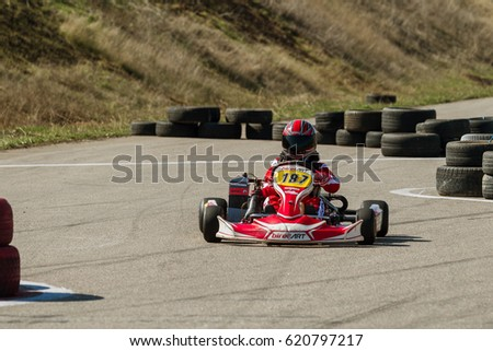 ODESSA, UKRAINE - April 2, 2017: Karting Championship. Pilots carting pilot in helmet, racing suit participates  card race. Karting show. Children, adult racers in karting. Blur motion with broaching