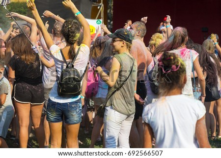 ODESSA, UKRAINE - August 5, 2017: Young people, boys and girls have fun doing selfie during festival of Holi by throwing coloured powder at each other. Festival of Colored Paint, colors. Color fest  #692566507
