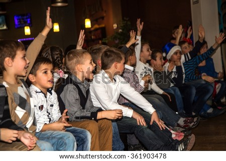 Odessa, Ukraine - December 25, 2015: Parents with children in audience during concert of creative demonstration performance karate club. Scene, audience emotionally to watch performances of athletes.