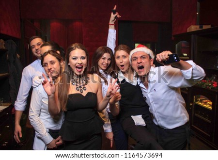 Odessa, Ukraine December 31, 2015: People smiling and posing on cam during concert in night club party. Man and woman have fun at club. Boy and girl at night club party #1164573694
