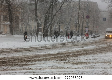 ODESSA, UKRAINE-January 16, 2018: Strong snowfall, cyclone in city streets in winter. Cars are covered with snow. Slippery road. Bad weather in winter: heavy snow and snowstorm. Pedestrians go on snow #797038075