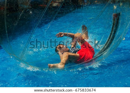 Odessa, Ukraine - July 11, 2017. Little children in an inflatable balloon, having fun on the water. The ball in the water - fascinating summer attractions for children. Water zorbing. #675833674
