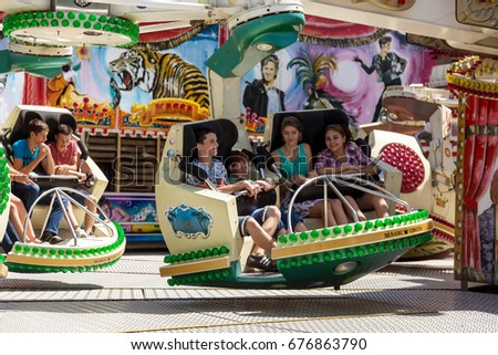 ODESSA, UKRAINE -11 July 2017: Youth entertainments in amusement park. Young friends, boys and girls have fun on exciting rides. Extreme rides - success in summer amusement park. Motion blur #676863790